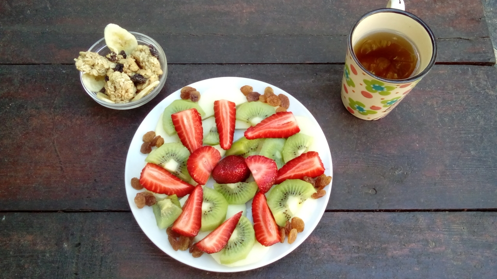 Obstteller mit Knuspermuesli und Tee